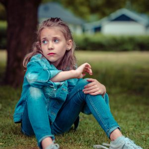 girl sitting on ground sad