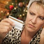woman holding credit card with Christmas background, looking anxious