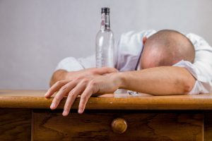 person passed out on a table with an empty bottle