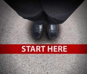 a business man is looking down at his feet with a red race line that says start here to represent a journey