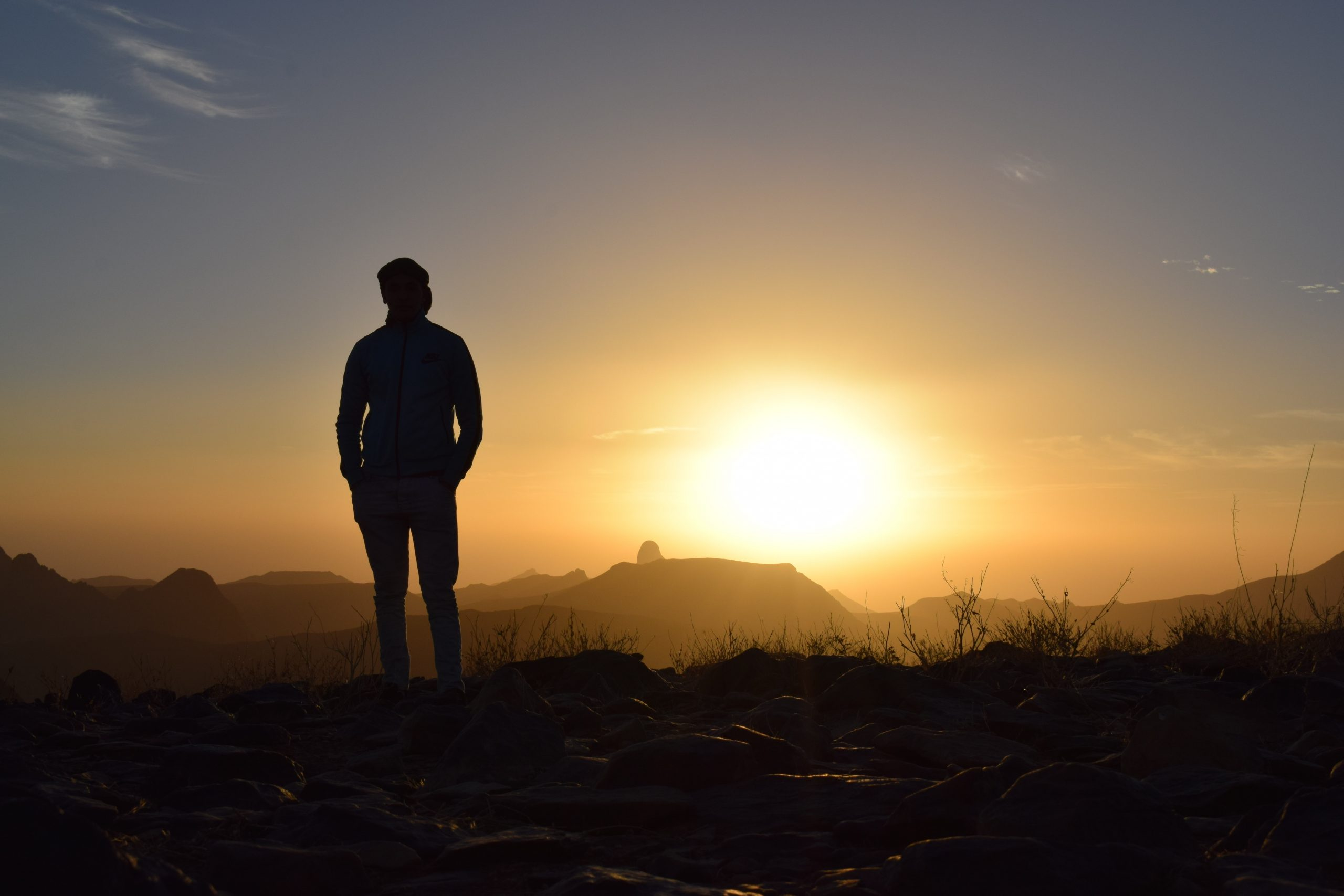 Man standing on top of mountain overlooking the sun - mental health during divorce